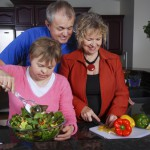 A mother, father, and a daughter with downs syndrom in the kitchen making a salad